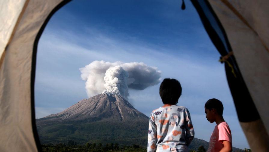 Туристы наблюдают из палатки, как извергается вулкан Синабунг в провинции Северная Суматра, Индонезия, 11 марта 2021 года