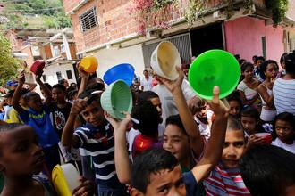 Дети стоят в очереди за бесплатной едой в бедном районе Каракаса, сентябрь 2016 года