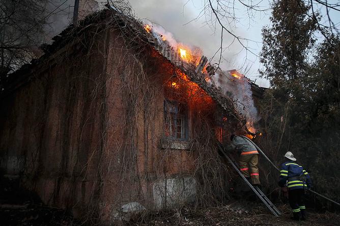 Пожарные гасят пожар в здании после обстрела