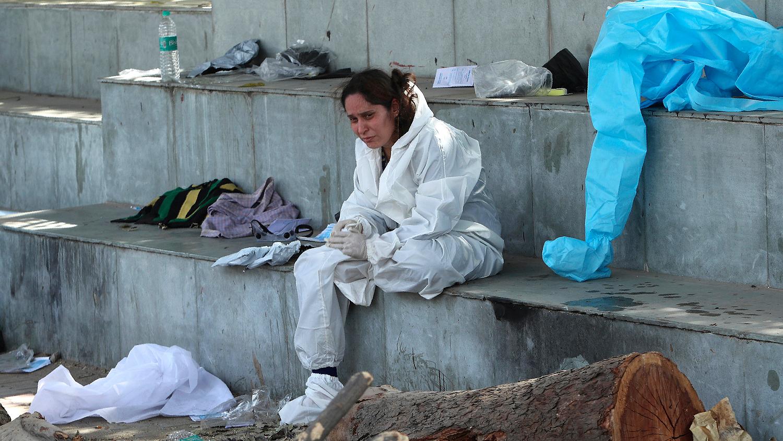 Девушка скорбит по умершему родственнику в крематории в Джамму