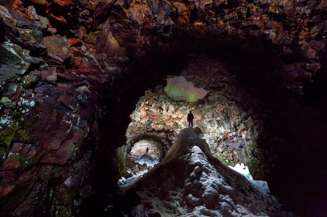 Этот кадр удалось сделать во время прогулки по исландской пещере высотой в 1,3 км. В некоторых местах «крыша» этой пещеры осыпалась, а через образовавшиеся отверстия в нее засыпался снег. Кроме того, через это отверстие можно видеть северное сияние, которое и является основным сюжетом этой фотографии