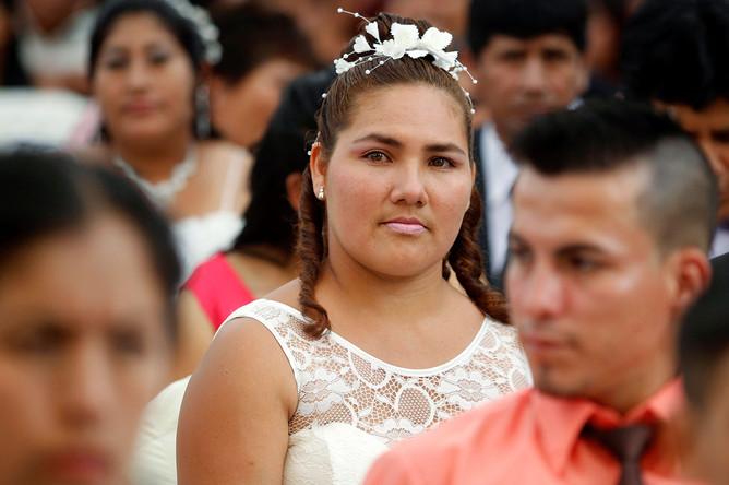 Одна из невест на массовой свадьбе в Перу. В торжественной церемонии, состоявшейся в Лиме, приняло участие 67 пар