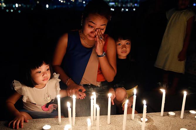 Женщина плачет над свечами, зажженными в память о погибших, Малайзия
