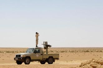 Солдат ливийской армии смотрит в бинокль во время патрулирования территории на окраине города Сирт