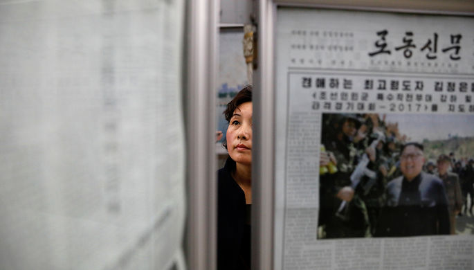Девушка в метро Пхеньяна около стенгазеты, 14 апреля 2017 года