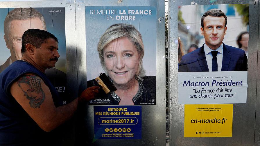 Постеры кандидатов на президентских выборах во Франции Марин Ле Пен и Эммануэля Макрона в городе Антиб, 14 апреля 2017 года