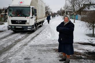 Автомобиль с логотипом Немецкого Красного Креста и местная жительница в Авдеевке, 6 февраля 2017 года