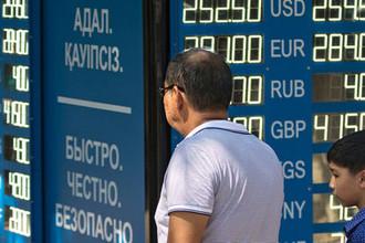 Мужчина с ребенком у информационного табло обменного пункта валюты в Алма-Ате.