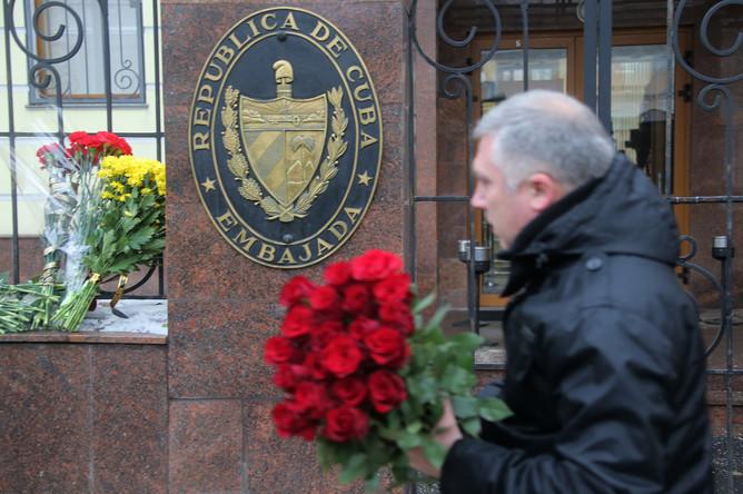 Мужчина несет цветы к посольству Кубы в Москве