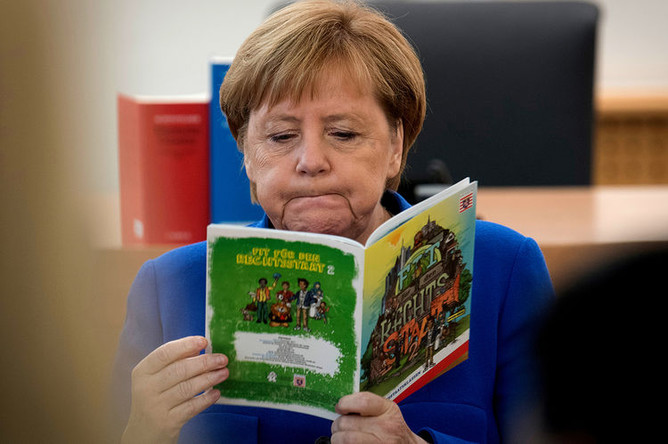 Канцлер ФРГ Ангела Меркель с брошюрой во время посещения занятий для мигрантов во Франкфурте, октябрь 2018 года