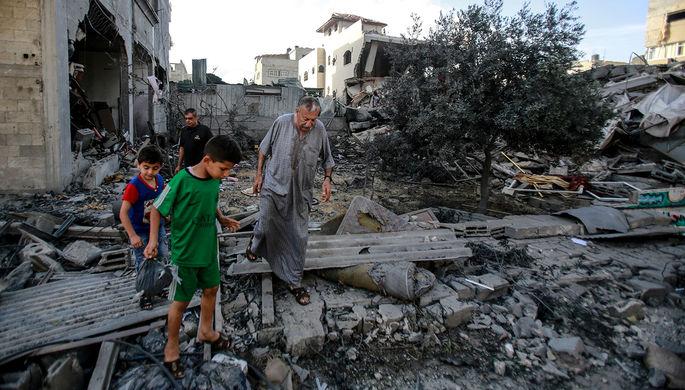 Местные жители ходят по завалам разрушенного в результате бомбардировки здания в секторе Газа, 17 мая 2021 года