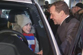 Председатель правительства РФ Дмитрий Медведев и олимпийская чемпионка по фигурному катанию у Дома правительства РФ после церемонии вручения автомобилей российским спортсменам, 28 февраля 2018 года