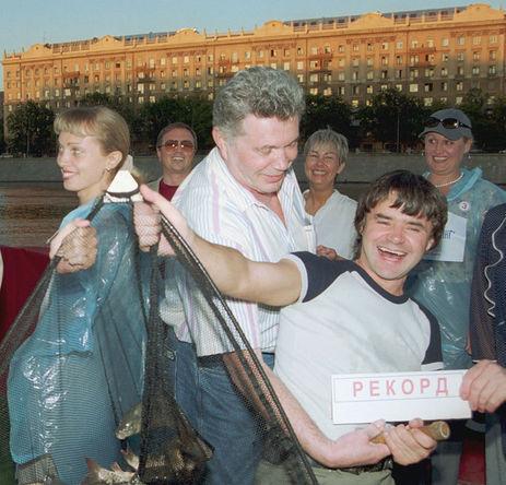 Певец Евгений Осин демонстрирует рекордный улов во время вечеринки в плавучем ресторане в Москве, 2001 год