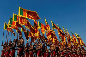 Военнослужащие с национальными флагами во время парада в городе Коломбо, столице Шри-Ланки, 2018 год
