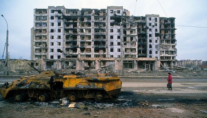 Остатки бронетехники и разрушенный дом в городе Грозном во время Чеченского конфликта 1994-1996 годов