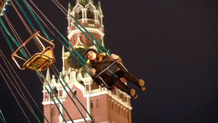 Девушка катается на карусели на фестивале «Путешествие в Рождество» на Красной площади в Москве.
