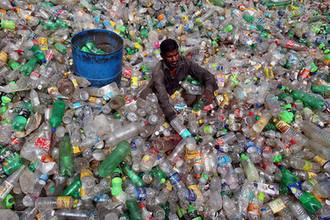 Мужчина сортирует бутылки на свалке пластика в Чандигархе (Индия)
