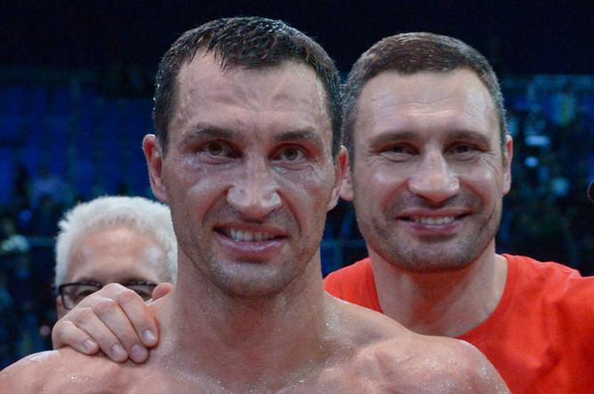 Владимир Кличко радуется победе в бою за титул чемпиона мира по версиям WBA, IBF, WBO и IBO, справа — его брат Виталий Кличко