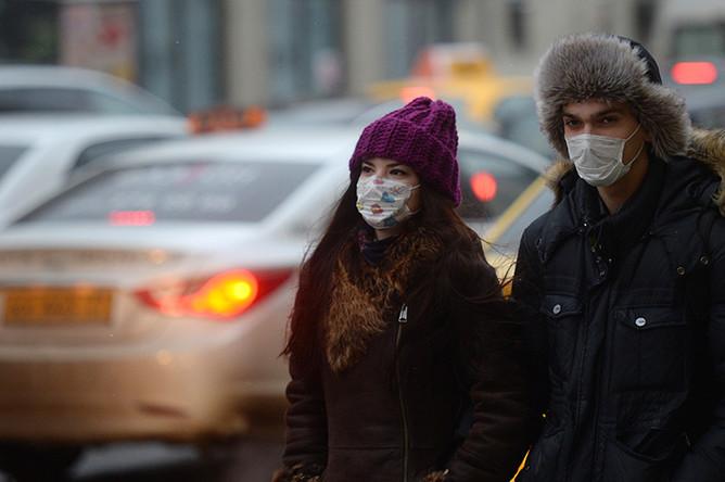 Жители Москвы в защитных масках на одной из улиц города