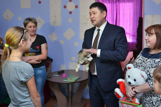 Полномочный представитель главы Республики Хакасия Михаил Побызаков передает школьнице из села Белый Яр щенка хаски, подаренного президентом Путиным