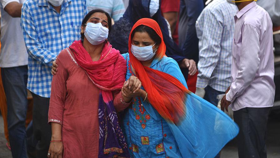 Родственники и близкие погибших во время массовой кремации жертв пандемии в Дели