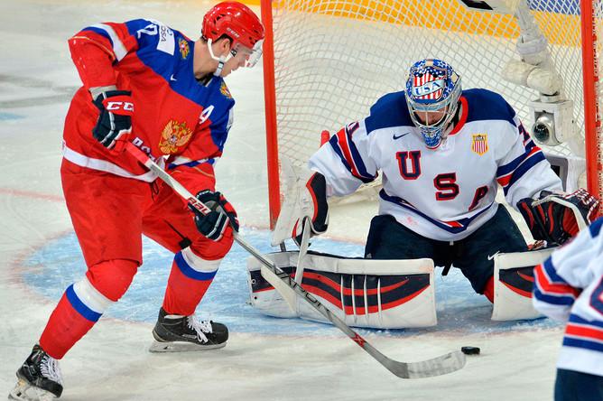 Игрок сборной России Павел Красковский (слева) и вратарь сборной США Алекс Неделькович в полуфинальном матче плей-офф молодежного чемпионата мира по хоккею между сборными командами России и США