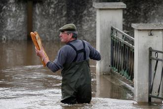 Житель несет французские багеты в затопленный дом своей матери после того, как дождь вызвал наводнение в предместье Орлеана, Франция