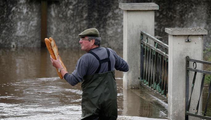 Житель несет французские багеты в затопленный дом своей матери после того, как дождь вызвал...