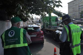 Сотрудник АМПП и инспектор МАДИ готовят автомобиль к эвакуации
