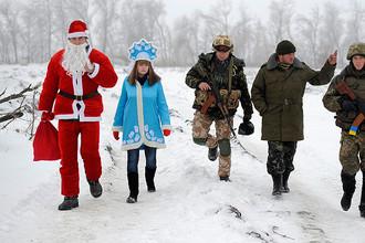 Местные жители в одежде Деда Мороза и Снегурочки во время посещения КПП украинской армии около Лисичанска в Луганской области, 2 января 2015 года