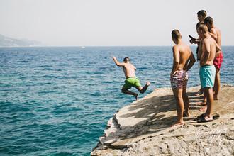 Отдыхающие прыгают со скалы недалеко от пляжа Могрен в Будве, Черногория
