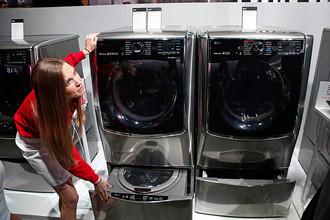 Сотрудник показывает стиральную машину, которой можно управлять с помощью смартфона. Стенд IG