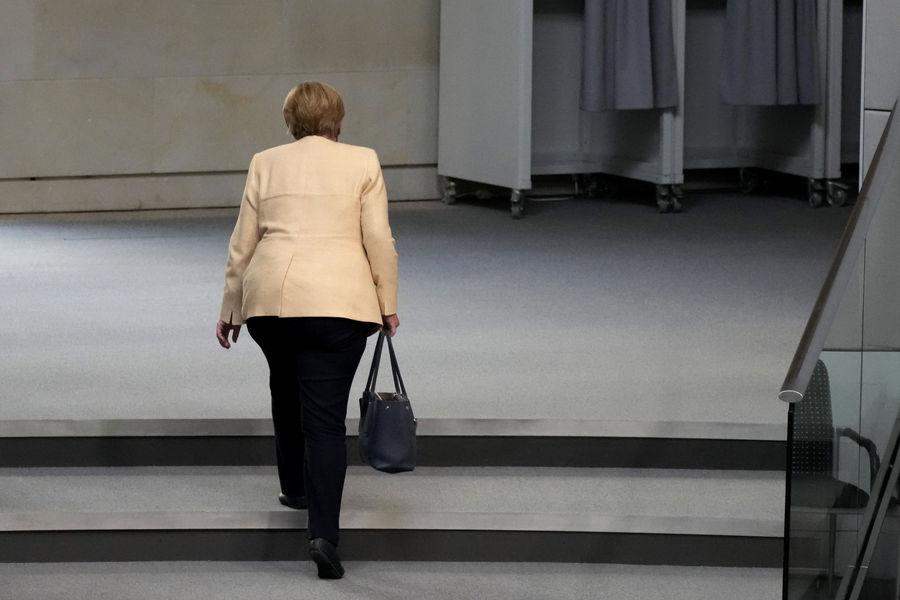 Ангела Меркель покидает зал пленарных заседаний