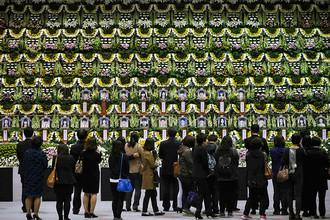 Люди у алтаря в память о жертвах крушения парома «Севол»