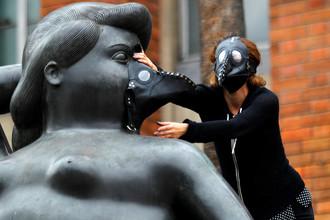 Группа экологов надевает противогазы на скульптуры художника Фернандо Ботеро, протестуя против высокого уровня загрязнения воздуха в Медельине, Колумбия