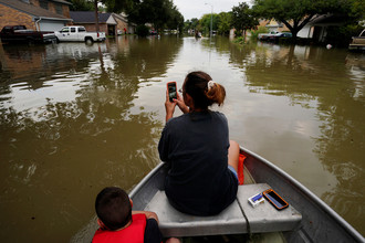 Женщина с сыном рядом с родительским домом во время наводнения в северо-западной части Хьюстона, Техас, 30 августа 2017 года