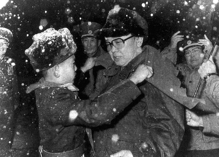Ким Чен Ир и ребенок, дарящий ему шарф, в школе для сирот в Пхеньяне, 1997 год