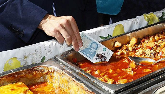 Глава Банка Англии Марк Карни показывает журналистам преимущества новой пластиковой банкноты перед обычной из бумаги
