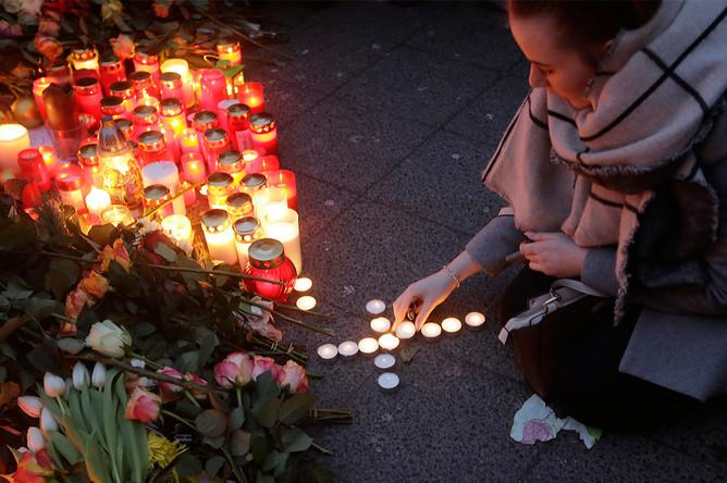 Свечи и цветы около рождественской ярмарки на площади Брайтшайдплац в Берлине, 20 декабря 2016 года