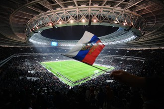 Болельщик на трибуне стадиона «Лужники» машет флажком во время товарищеского матча между сборными командами России и Аргентины.