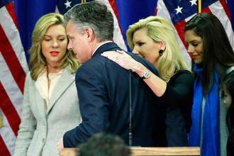 Джон Хантсман в окружении жены и дочерей покидает сцену после заявления о выходе из президентской гонки, 2012 год