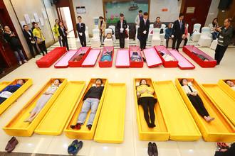 Посетители лежат в гробах в день открытых дверей в похоронном бюро в городе Чунцин, Китай, апрель 2017 года