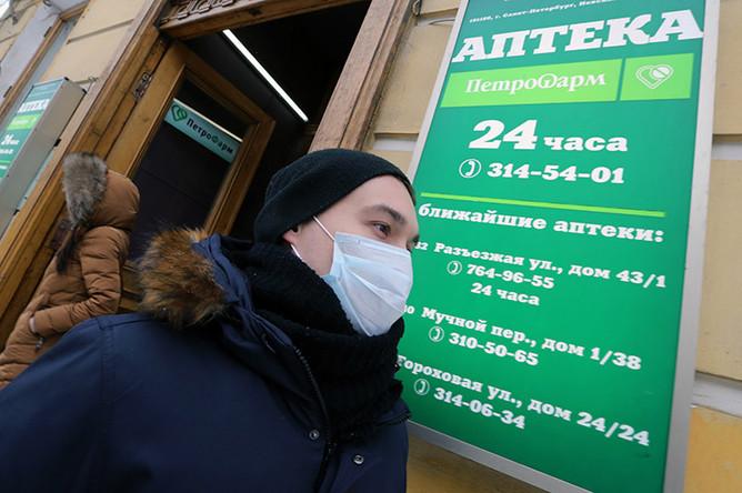 Житель Санкт-Петербурга в защитной маске у входа в аптеку