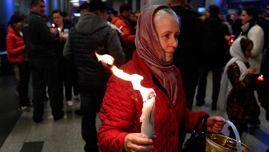 Верующие со свечами, зажженными от Благодатного огня в аэропорту Внуково