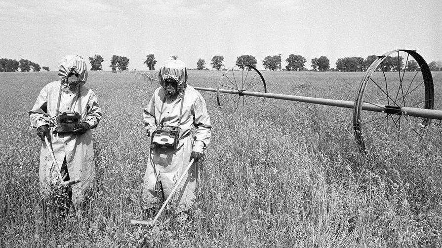 Дозиметристы в специальных костюмах проводят контроль радиации на полях в районе аварии на Чернобыльской АЭС, июнь 1986 год