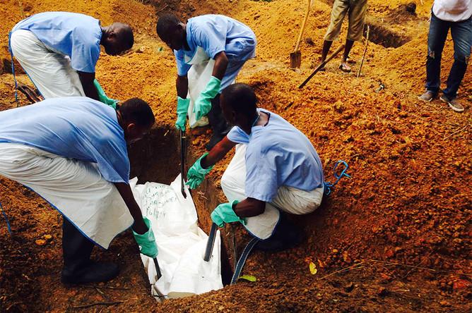 Волонтеры в Сьерра-Леоне хоронят погибшего от лихорадки Эбола мужчину, предварительно убедившись, что его тело не представляет опасности для окружающих