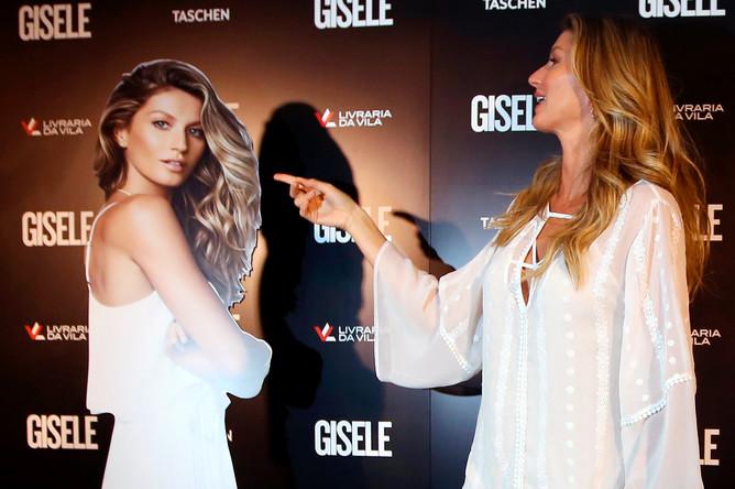 Бразильская модель Жизель Бундхен с экземпляром своей книги на презентации в Сан-Паулу