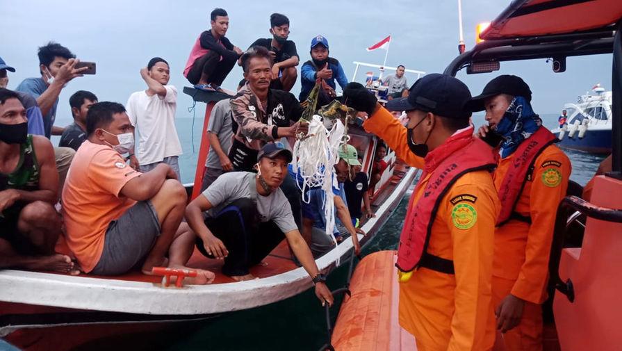 Местные рыбаки и спасатели на месте крушения самолета авиакомпании Sriwijaya Air около Джакарты, 9 января 2021 года