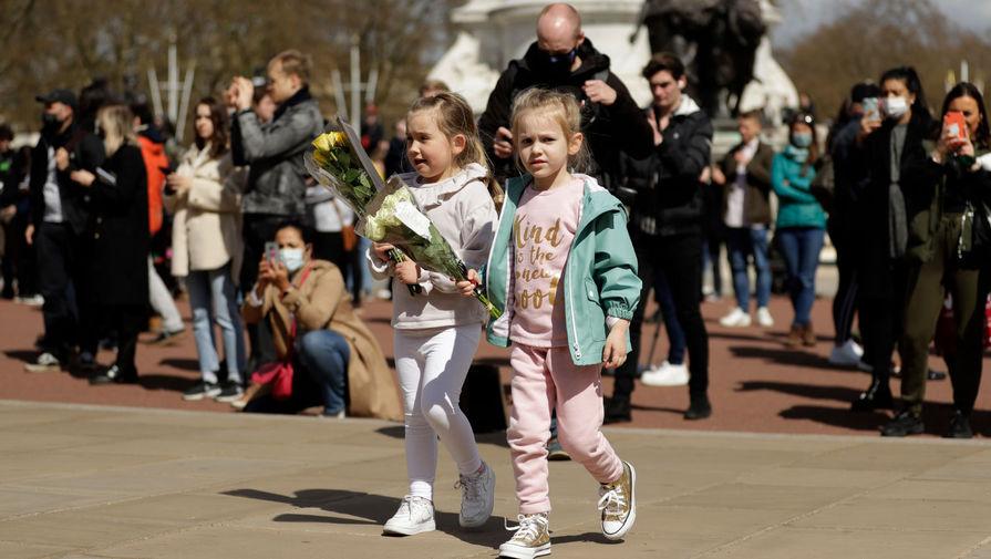 Дети несут цветы к Букингемскому дворцу в Лондоне в память о принце Филиппе, 9 апреля 2021 года