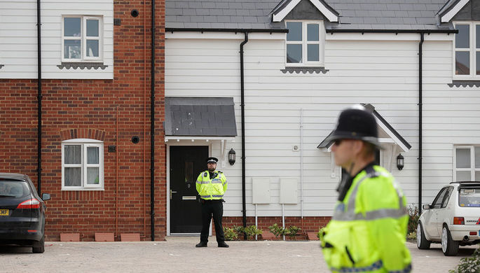 Сотрудники британской полиции около оцепленной территории после инцидента с отравлением в Эймсбери...